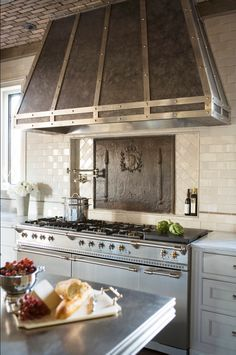 The vent hood was custom designed and then constructed by a local blacksmith out of zinc and steel.    The 38.5″ wide x 32″ tall iron piece behind the range is an antique Iron fire back dating to 1788 from France.