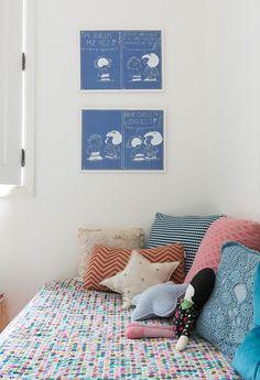 Quarto infantil tem cama com roupa de cama estampada e almofadas com diferentes cores e formatos.