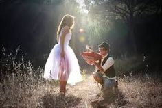it is an image of a girl and a boy in the forest and the boy is kneeling down to the girl