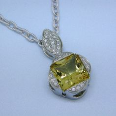 Eye-catching modern pendant with a traditional twist. 14 karat White Gold with a spectacular 5.42ct. princess cut yellow Beryl.