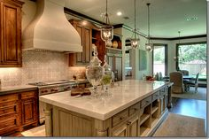 Houstonian Maria Tracy used white marble on the island which was custom built to look like an antique shop cabinet.  The tiles on the backsplash can be either antique or reproductions, similar concrete tiles can be found at Chateau Domingue.