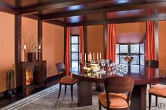 Cinnabar-color fabric warms the walls and windows of the jewel-box dining room, which features an Armani/Casa table and carpet.