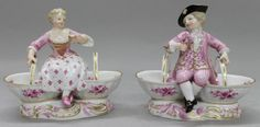 A Pair of Meissen Porcelain Figural Sweetmeat Dishes, depicting a boy and girl in 18th century attire resting atop the segmented bowls, having crossed swords mark in blue underglaze with further impressed and incised marks. Height 4 7/8 x width 5 3/4 inches.