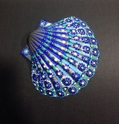 Hand painted scallop shell. Painted by me in quality acrylic paints and varnished to give it a beautiful finish. It is an original design incorporating blue green and white acrylic paints and silver metallic acrylic paint to enhance the finish. Clean gently with a soft damp cloth when