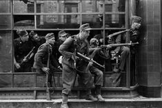 Warsaw Uprising: SS soldiers from Dirlewanger Brigade in window of townhouse at Focha 9 Street. In the glass reflection one can see details of the townhouse on the opposite side of the street at Focha 8 Street. Photo: Bundesarchiv. http://wrhstol.com/2ErmBy7