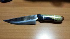 Coltello full tang in acciaio c 70 con manico in mogano e resina bicolore giallo-azzurro. Perni-pin e separatori in acciaio inox.