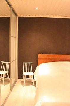 Makuuhuoneen tehosteseinä Tierrafino savimaali harmaana sisältäen mustaa kiveä.