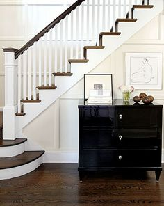 Staircase - side view of dark steps and railing with white spindles. Also love the wall molding!