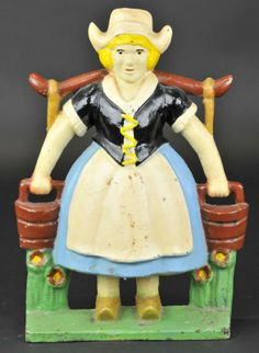"""DUTCH MILKMAID WITH PAILS DOORSTOP Littco Products, original label intact, bright and bold colors, depicts a maid holding two milk pails in traditional clothes. 13 1/8"""" h. (Pristine-Near Mint Cond.)"""