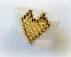 White Ring With Gold Heart. Beadwoven Ring, Valentine's Day Gift Under Not the top bead. Beaded Rings, Beaded Jewelry, Diy Jewelry, Bead Loom Bracelets, Handmade Rings, Bijoux Diy, Beads And Wire, Bead Jewelry, Wire Wrapped Rings