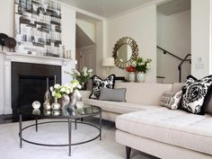 Modern art, a contemporary sectional and an elegant black and white color palette give this gorgeous living room a feeling of opulence. Silver accents throughout the room bring the entire look together.
