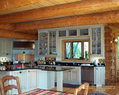 Kitchen in a handcrafted log home I designed in Michigan  For more photos or this or any other or my homes, please check out my website, www.designma.com, my Design Page, www.facebook.com/loghomedesign  #loghomes #loghomedesign #loghomekitchen #handcraftedloghomes
