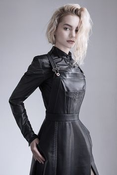 Black leather overall dress crocodile embossed inlay on the chest, paired with a black button-up leather shirt with snakeskin detailing at the collar.  The small details of this outfit elevate it from a look that was already unique to something completely rare and couture.