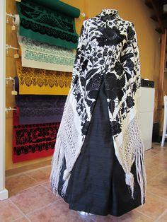 Mantón antiguo de tulipán color marfil bordado en negro sobre saya negra de seda.
