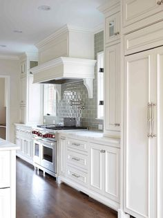 Love this kitchen- -White Kitchen 1 of 2 -Like hardwood floor color -white paneled hood with swing arm pot filler -wolf stove -cabinets installed over DOUBLE door refrigerator -subway tile kitchen design design decorating design ideas Kitchen Redo, New Kitchen, Kitchen Remodel, Kitchen White, Kitchen Cabinets, Kitchen Ideas, Kitchen Faucets, Kitchen Stove, Kitchen Designs