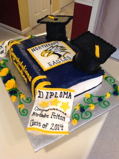 Graduation cake. Book cake with two grad cap on top of the book and two diplomas. This cake is made with buttercream frosting. The diplomas are made out of fondant b