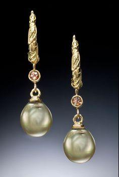 Green Pearl and Andaluzite Hoop Earrings by Conni Mainne. 18k yellow gold hoops are cast and fabricated with latch-back closures. 8mm pearls are natural green colored freshwater pearl. Andaluzites (gems that change colors from cinnamon to moss green) are tube-set. These earrings may be custom ordered with a wide variety of gems or pearl colors. Please contact our Customer Care department for more information.