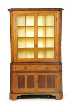 "AMERICAN CORNER CUPBOARD. Mid 19th century, curly maple, walnut and pine. Two-piece cupboard: two doors on top with eight panes of glass each and two paneled doors below. Two dovetailed drawers with scroddleware handles. Reeded molding. 87""h. 54""w. 18""d."