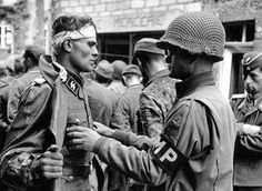 US Military Police Lt. Paul Unger searches POW Untersturmführer (lieutenant) Waffen SS Kurt Peters of the Regiment of 17 Panzer Grenadier Division at Notre-Dame-de-Cenilly, 27 July (Photo: Robert Capa)