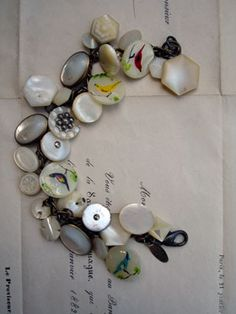 Mother of Pearl Bird Button Repurposed Bracelet  It started with those amazing bird buttons. They were kind of ridiculously expensive but I loved them and bought them and immediately this bracelet popped into my head. I pulled out all my MOP stuff - buttons, cufflinks, etc. and went at it!   So, the stars of this bracelet are...