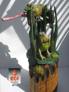 ( TOTEK )  WAWARONS  ...here is the sculpture that is called (wawarons). 2 large / 5 little frogs on lilys in a watertight with cattails (in one piece of wood) (12''x 36'')