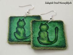 """Kolczyki z kolekcji """"Kocie sny"""" - kwadraty o przekątnej/średnicy 5,5 cm, z drewnianej sklejki, ręcznie malowane farbą akrylową z obu stron, w odcieniach zieleni, z motywem kota, zabezpieczone lakierem, zdobione sznurkiem jutowym, na otwartych biglach. Dzieło Wielkiego Słonia w Czerwone Paski."""