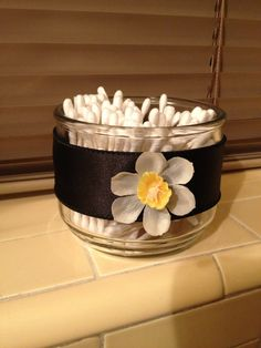 Use empty candle jars for cute storage. I'm not liking the ribbon & flower, but I like the storage idea:) Empty Candle Jars, Glass Jars, Candles, Mason Jars, Small House Decorating, Decorating Tips, Dyi Crafts, Home Crafts, Vintage Bathroom Accessories