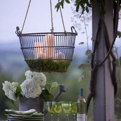 Outdoor lighting made from a hanging planer basket lined with moss and filled with candles (regular or the battery operated ones)