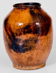 """Crocker Farm 3/25/17 lot #242 (side 1).  Realized: $2,124 ($1,800).  10"""" h. Glazed Redware Jar with Streaked Manganese Decoration, Bristol County, MA, early 19th c., distinctive tapered shoulder, footed base & narrow opening, with manganese streaks over a bright-orange ground & clear lead glaze. Excellent color. Base chips. A few flakes on underside. Light rim wear & a shallow 1"""" rim chip. Glazed surface survives in remarkable condition. Provenance: Dr. Raymond L. Owen Collection."""