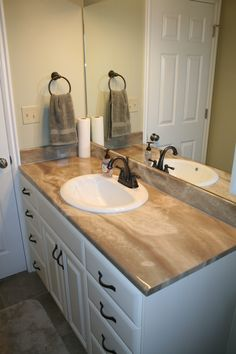 Bathroom Remodel: Bronze faucet, stone counter tops, large mirror, white cabinets with bronze handles.