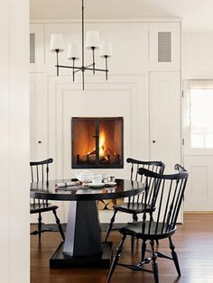 In the kitchen, such a cool idea to have an eye level fireplace by the table...<3 the fireplace...
