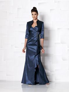 @Amy VaninTwo-piece stretch taffeta suit, sleeveless A-line dress with shoulder straps, sweetheart neckline, bodice features side pleating accented with hand-beaded motif, side slit trimmed with cascading ruffle, matching bolero jacket with three-quarter length sleeves. Sizes:4 – 20