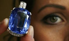 A model displays a 202.82 carat sapphire pendant during a preview at Sotheby's auction house in Geneva
