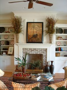 Brick Fireplace w/ mantle & built-ins and I love the floral arrangements on the mantle!