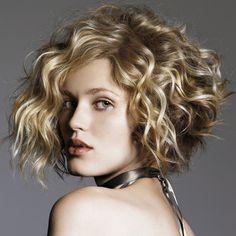 Pour donner beaucoup de volume à cette coiffure, les cheveux frisés de cette jeune femme ont été coupés au carré, mais le coiffeur a dégradé les longueurs. Il a ensuite séché la chevelure en la gonflant, ce qui donne un résultat splendide. La coloration aux différentes nuances de châtain est très réussie.