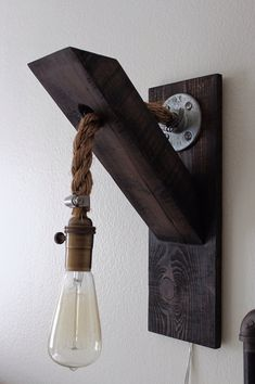 Here is a rugged industrial sconce. Made with solid reclaimed lumber, and manila rope. Great looking sconce, and looks amazing when sold as a pair.