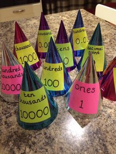 Place Value hats. Each hat has one label. Ones, tens, hundreds, thousands, hundred thousands, decimal point, tents, hundredths, thousandths etc. Go as far as you need. Each child wears a hat and hold one digit. Can be used to show hoe to multiply or divide by 10, 100, 1000 etc. Make big and small numbers. Secure place value knowledge. I used basic party hats. Post it notes. Sharpie pen. Shire seal.