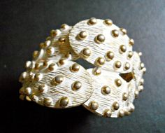 This is white bracelet that is a hinged cuff in a prickly pear cactus design...maybe a Tortolani.    A gorgeous and substantial bracelet with the
