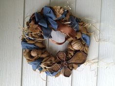 Camel colored burlap cross wreath with denim blue, brown and cream embellishments.