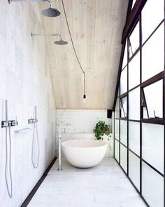 If I could design a bathroom, I think it would look something like this. Lots of frosted glass for privacy and natural light, a large freestanding tub, and plants!