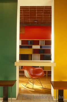 An Eames rocking chair stands before a wall of shelves in an open doorway. Brightly coloured modular shelving in the kitchen can be seen through the large serving hatch between two vividly painted walls. Photographer: Jacques Dirand Designer/Stylist: Architect: Le Corbusier Location: the Jaoul House, Paris