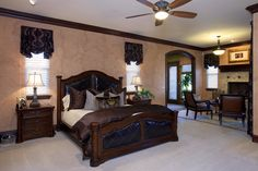 Master bedroom with dual windows, formal fireplace setting and wood crown molding along ceiling