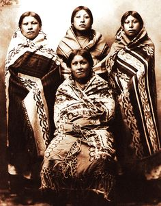 """Four young women wrapped in blankets, circa 1890. From """"Language of the Robe,"""" courtesy of Western History Collections, University of Oklahoma library."""