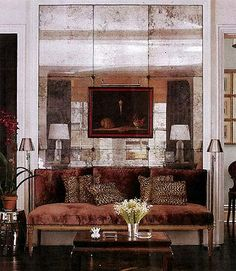 In the living room of his home, interior designer Todd Romano created a wall of antique mirrored mercury-glass panels that serves as a backdrop for the seating area as well as for a 1950s still-life painting. The Louis XVI banquette and antique Chinese lacquered table add to the old-world glamour of the space. via The Enchanted Home: Lusting for leopard!