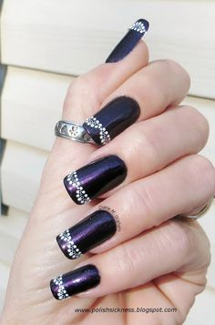 Fabulous nails! With a dark blue/black base color with what looks like a purple stripe in the middle. To finish the art. Use some dotting tools!