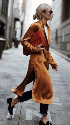 Burnt orange midi-length jacket, frayed skinny jeans, black loafers, and red clutch bag. With low bun and round sunglasses.