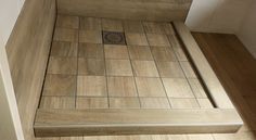 Een douchebak van keramische tegels met houtlook.