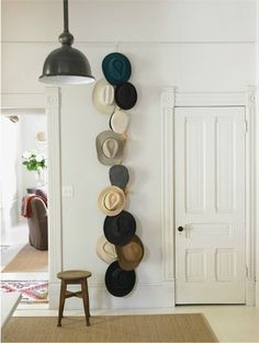 This vertical hanging hat display from House Beautiful is an intriguing and practical way to display a collection of items you reach for often. Try this: Rest a hook on a high molding, loop a long ribbon or cord onto it, and attach additional hooks onto the ribbon where you'd like each hat to hang. A small stool beneath the arrangement lets you reach for the highest ones.
