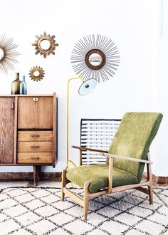 Midcentury, eclectic reading nook with wall decals, retro credenza, and vintage green armchair