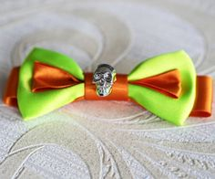 The Mean Machine Bow Tie: Made from aluminous green and orange satin materials which really capture the eye.  With its use of super bright colours combined with a metal skull centre piece to make this bow tie have enchanting yet dangerous look about it standout against the crowd and dare to wear this spectacular Bow tie!  #badassarange #badasspugclub #ilovepugs #leather #black #rebel #bows #bowsofinstagram #instabow #petbow #dogbow #dogbowtie #dogaccessories #bling #love #dark #bad #rocker…